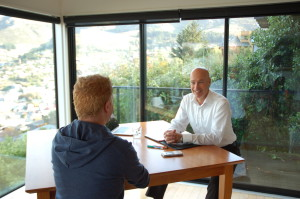 Photograph of David Bennett, business coach sitting at a table talking to a client during a coaching session, with a view of Lyttelton through the window in the background.